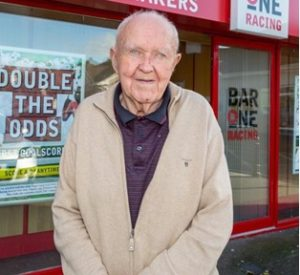 Denis O'Connor Who Fight Off Robbers Courageously is Standing Outside the Bar One Racing Shop